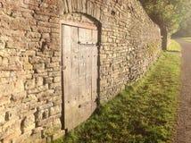 Oude steenmuur met deur Stock Afbeelding