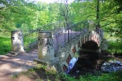 Oude steenvoetgangersbrug met vermakelijke graffititekeningen stock afbeelding