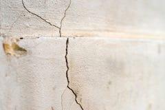 Oude stichting en pleistermuur met barsten De bouw vereisend reparatieclose-up stock foto's
