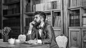 Oude stijl en mannelijke manier De gebaarde mens zit in bibliotheek met oud boek De rijpe mens in slim kostuum denkt Professor me royalty-vrije stock foto