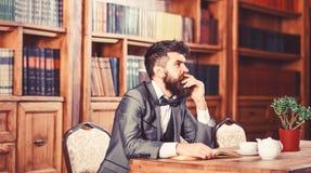 Oude stijl en mannelijke manier De gebaarde mens zit in bibliotheek met oud boek De rijpe mens in slim kostuum denkt Professor me royalty-vrije stock foto's