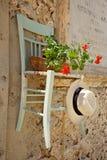 Oude stoel die aan een muur wordt gehangen Stock Foto's