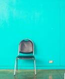 Oude stoel op concrete groene muur Royalty-vrije Stock Afbeeldingen