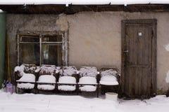 Oude stoelen dichtbij het huis onder de sneeuw Stock Afbeelding