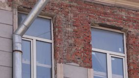 Oude stoffige huisvoorgevel met bakstenen muur en paar van vensters in daglicht stock footage