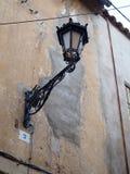 Oude straat lampin een vuile muur stock afbeeldingen