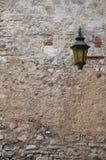 Oude straatlantaarn op een muur stock afbeelding