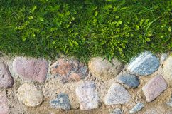 Oude straatstenen in zeldzame stenen in zand met gras Royalty-vrije Stock Afbeelding