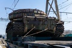 Oude tank met artisanaal reactief pantser op een spoorweglage goederenwagon stock fotografie