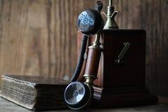Oude telefoon en retro boek op een hout Stock Afbeeldingen