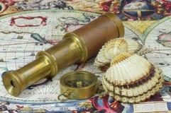 Oude telescoop, kompas, zeeschelp en uitstekende kaart van de wereld Stock Fotografie