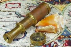 Oude telescoop, kompas, zeeschelp en uitstekende kaart van de wereld Stock Afbeelding