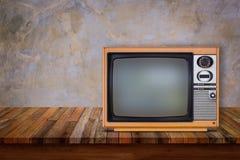 Oude televisie op houten lijst stock afbeeldingen