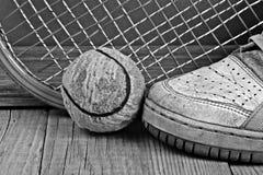 Oude tennisbal en tennisschoenen Stock Fotografie