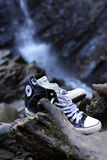 Oude tennisschoenen op een achtergrond van rotsen en waterval Royalty-vrije Stock Afbeeldingen