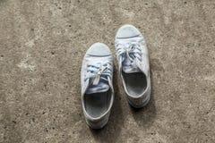 Oude tennisschoenen op fundamenteel het beton stock foto