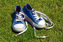 Oude tennisschoenen op grasachtergrond Stock Foto