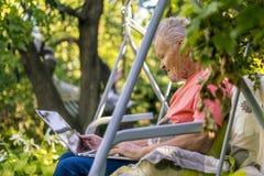Oude teruggetrokken mens die aan computer in de tuin van het de zomerplattelandshuisje werken stock foto