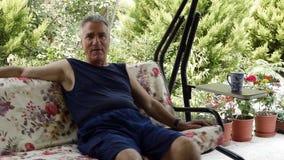 Oude teruggetrokken mens op schommeling stock footage