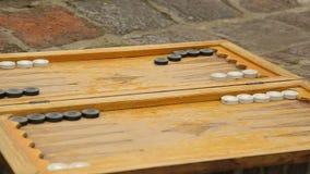 Oude teruggetrokken mensen die backgammon in de werf spelen buiten, het plezier van raadsspelen stock footage
