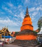 Oude Thaise Boeddhistische pagode die met oranje robes wordt verpakt stock foto