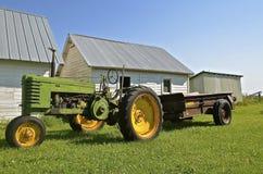 Oude tractor die een roestige mestverspreider trekken stock foto's