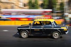 Oude traditionele zwarte en gele taxi in beweging die met panning van het motieonduidelijke beeld wordt afgeschilderd royalty-vrije stock foto