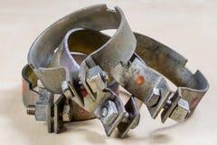 Oude tuintoebehoren Roestige slangklemmen op de workshoplijst stock foto