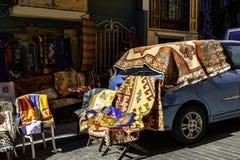 Oude Turkse dekens en tapijten voor verkoop, uitstekende winkel in het district van Cukur Cuma Caddesi, Istanboel stock foto's