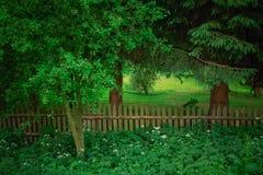 Oude type landelijke tuin met houten fance, volledig van bomen en gree Stock Afbeeldingen