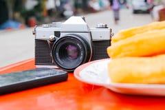 Oude Uitstekende Analoge Camera op de Lijst met Telefoon en Youtiao stock fotografie