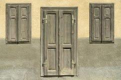 Oude uitstekende deur en vensters op aardachtige gekleurde muur Stock Afbeeldingen