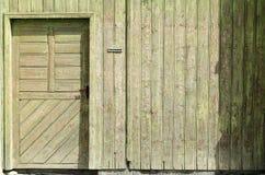 Oude uitstekende deur op een houten muur Stock Afbeelding