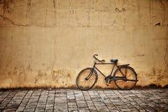 Oude uitstekende fiets dichtbij de muur Royalty-vrije Stock Afbeeldingen