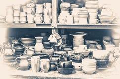 Oude uitstekende foto Velen verschillend aardewerk die zich op de planken in een workshop bevinden Stock Afbeeldingen
