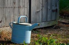 Oude uitstekende gieter in de tuin Stock Afbeelding