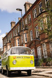 Oude uitstekende groene die bestelwagen in een straat met victorian huizen wordt geparkeerd royalty-vrije stock afbeelding
