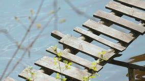 Oude, uitstekende houten brug, pijler op de achtergrond van kleine golven van het water van het meer, rivier stock footage