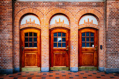 Oude uitstekende houten deuren en bakstenen muur bij station in Cope Stock Foto's