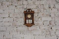 Oude Uitstekende houten klok op de bakstenen muur royalty-vrije stock fotografie