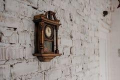 Oude Uitstekende houten klok op de bakstenen muur stock afbeeldingen