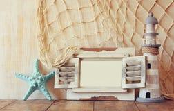 Oude uitstekende houten witte kader en vuurtoren op houten lijst wijnoogst gefiltreerd beeld zeevaartlevensstijlconcept Royalty-vrije Stock Foto's