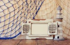 Oude uitstekende houten witte kader en vuurtoren op houten lijst wijnoogst gefiltreerd beeld zeevaartlevensstijlconcept Royalty-vrije Stock Afbeelding