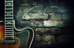 Oude uitstekende jazzgitaar op een bakstenen muurachtergrond De ruimte van het exemplaar Achtergrond voor overleg, festivallen, m royalty-vrije stock afbeelding