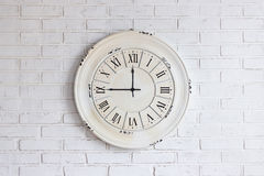 Oude uitstekende klok op bakstenen muur Stock Fotografie