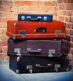 Oude uitstekende koffers die dichtbij bakstenen muur worden geïsoleerde Stock Foto