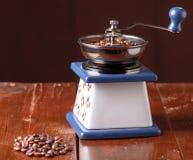 Oude uitstekende koffiemolen en gemorste geroosterde hete bonen Stock Afbeeldingen