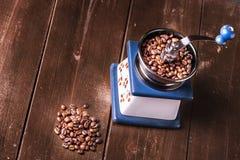 Oude uitstekende koffiemolen en gemorste geroosterde hete bonen Royalty-vrije Stock Foto
