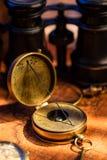 Oude uitstekende retro kompas en kijker op oude wereldkaart stock foto