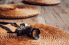 Oude uitstekende retro stijlcamera op de droge achtergrond van de de mat natuurlijke textuur van de waterhyacint royalty-vrije stock fotografie